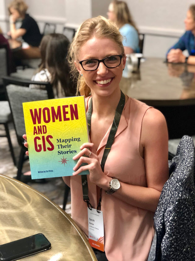 Attendee holding up a Women and GIS book that she received for presenting.